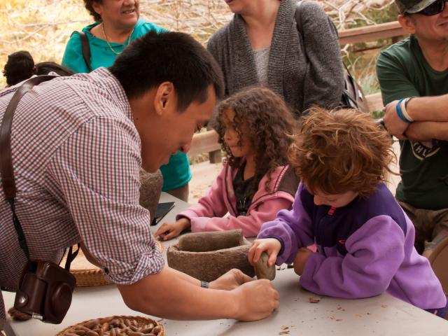 Image of UC Davis student teaching a young participant at one of the many free public programs offered by the UC Davis Arboretum and Public Garden.