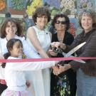 Group of people cutting ribbon in front of the mosaic mural of the Nature's Gallery Court.