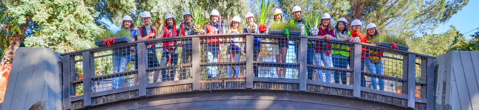 Image of the Learning by Leading Waterway Stewardship team on a bridge over the Arboretum Waterway.